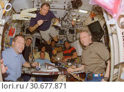 Купить «EARTH Abaord the International Space Station -- 13 Dec 2006 -- The STS-116 and Expedition 14 crewmembers share a meal in the Zvezda Service Module of the...», фото № 30677871, снято 21 мая 2019 г. (c) age Fotostock / Фотобанк Лори