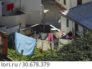 Купить «PORTUGAL Nazare -- An elderly lady in her garden as her washing dries in Nazare Portugal -- Picture by Jonathan Mitchell/Atlas Photo Archive.», фото № 30678379, снято 25 января 2015 г. (c) age Fotostock / Фотобанк Лори