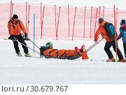 Купить «Спасатели Камчатского спасательного отряда эвакуируют пострадавшего (получившего травму) горнолыжника со склона горы на спасательных носилках во время Чемпионата России по горным лыжам», фото № 30679767, снято 28 марта 2019 г. (c) А. А. Пирагис / Фотобанк Лори