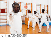 Купить «Sporty young man fencer practicing effective fencing techniques in training room», фото № 30680351, снято 11 июля 2018 г. (c) Яков Филимонов / Фотобанк Лори