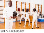 Купить «African american male fencer in uniform standing with mask and foil», фото № 30680359, снято 11 июля 2018 г. (c) Яков Филимонов / Фотобанк Лори