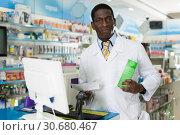 Купить «Male pharmacist offering medicines in pharmaceutical shop», фото № 30680467, снято 2 марта 2018 г. (c) Яков Филимонов / Фотобанк Лори