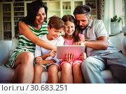 Купить «Parents with their children sitting on sofa and using digital tablet», фото № 30683251, снято 28 мая 2020 г. (c) Wavebreak Media / Фотобанк Лори