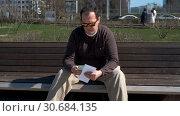 Купить «Middle age man sitting outdoors and counts cash», видеоролик № 30684135, снято 20 января 2020 г. (c) Антон Гвоздиков / Фотобанк Лори