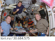Купить «EARTH Abaord the International Space Station -- 13 Dec 2006 -- The STS-116 and Expedition 14 crewmembers share a meal in the Zvezda Service Module of the...», фото № 30684575, снято 21 мая 2019 г. (c) age Fotostock / Фотобанк Лори