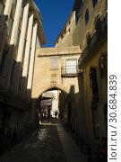 Купить «COIMBRA, PORTUGAL - August 13, 2016: Tourists explore the ancient lanes of the Almedina area in the historic university city of Coimbra, Portugal.», фото № 30684839, снято 13 августа 2016 г. (c) age Fotostock / Фотобанк Лори