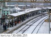 Купить «Пассажиры ожидают пригородную электричку на платформе Белорусского вокзала в небольшой снегопад. Москва», фото № 30686251, снято 4 марта 2019 г. (c) Александр Замараев / Фотобанк Лори