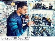 Male choosing baitcasting reel for rod for fishing in the sports shop. Стоковое фото, фотограф Яков Филимонов / Фотобанк Лори