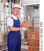 Купить «Mason installing red brick», фото № 30686599, снято 28 мая 2018 г. (c) Яков Филимонов / Фотобанк Лори