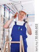 Купить «Electrician mounting electrical wiring», фото № 30686603, снято 28 мая 2018 г. (c) Яков Филимонов / Фотобанк Лори