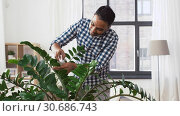 Купить «indian man cleaning houseplant's leaves at home», видеоролик № 30686743, снято 26 апреля 2019 г. (c) Syda Productions / Фотобанк Лори