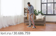 Купить «man in headphones with broom cleaning at home», видеоролик № 30686759, снято 26 апреля 2019 г. (c) Syda Productions / Фотобанк Лори
