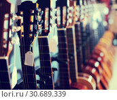 Купить «row of new acoustic guitars in music shop», фото № 30689339, снято 29 марта 2017 г. (c) Татьяна Яцевич / Фотобанк Лори