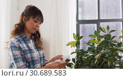 Купить «happy asian woman cleaning houseplant at home», видеоролик № 30689583, снято 25 апреля 2019 г. (c) Syda Productions / Фотобанк Лори