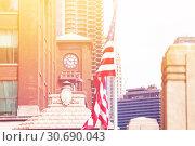 Купить «US flag over clocktower in downtown Chicago», фото № 30690043, снято 23 апреля 2018 г. (c) Сергей Новиков / Фотобанк Лори
