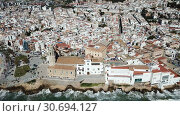Купить «Aerial view of Sitges small town with church on Mediterranean coastline, Spain», видеоролик № 30694127, снято 27 апреля 2018 г. (c) Яков Филимонов / Фотобанк Лори