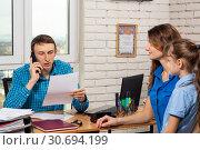 Купить «Офисный специалист звонит по телефону, на приеме мама с ребенком», фото № 30694199, снято 17 марта 2019 г. (c) Иванов Алексей / Фотобанк Лори