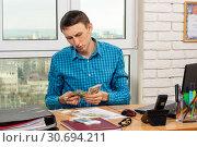 Купить «Молодой офисный работник считает деньги», фото № 30694211, снято 17 марта 2019 г. (c) Иванов Алексей / Фотобанк Лори