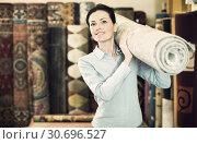 Купить «Female keep in hand colored carpet in interior shop», фото № 30696527, снято 22 ноября 2017 г. (c) Яков Филимонов / Фотобанк Лори