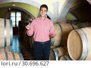 Купить «Laughing man owner of winery standing with wine», фото № 30696627, снято 21 сентября 2016 г. (c) Яков Филимонов / Фотобанк Лори