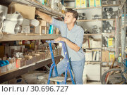 Купить «foreman is standing on the stairs near the shelves with boxes», фото № 30696727, снято 26 июля 2017 г. (c) Яков Филимонов / Фотобанк Лори