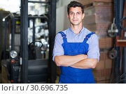 Купить «Portrait of thoughtful male in uniform on his workplace in building store.», фото № 30696735, снято 26 июля 2017 г. (c) Яков Филимонов / Фотобанк Лори