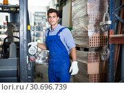 Купить «Portrait of calm male in uniform on his workplace in building store.», фото № 30696739, снято 26 июля 2017 г. (c) Яков Филимонов / Фотобанк Лори