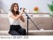 Купить «Female beautiful musician singing at home», фото № 30697335, снято 1 октября 2018 г. (c) Elnur / Фотобанк Лори