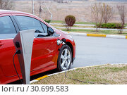 Купить «EV Car or Electric red car at charging station with the power cable supply plugged in on blurred nature with soft light background. Eco-friendly alternative energy concept», фото № 30699583, снято 30 марта 2019 г. (c) Happy Letters / Фотобанк Лори