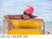 Купить «Довольная женщина в солнечных очках загорает на желтом шезлонге на пляже», фото № 30699783, снято 23 июля 2018 г. (c) Кекяляйнен Андрей / Фотобанк Лори