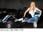 Купить «Smiling woman with helmet standing near cars for motor racing in sport club», фото № 30700179, снято 31 мая 2020 г. (c) Яков Филимонов / Фотобанк Лори