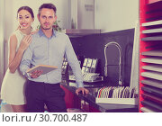 Купить «smiling married couple selecting kitchen furniture», фото № 30700487, снято 15 июня 2017 г. (c) Яков Филимонов / Фотобанк Лори