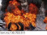 Купить «Сильный пожар, горят автомобильные покрышки, черный ядовитый дым в небе», фото № 30703511, снято 18 апреля 2019 г. (c) А. А. Пирагис / Фотобанк Лори