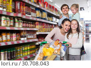 Купить «Smiling family with two daughters shopping», фото № 30708043, снято 25 мая 2019 г. (c) Яков Филимонов / Фотобанк Лори