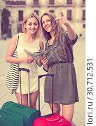 Купить «Two girls with luggage at street», фото № 30712531, снято 26 июня 2019 г. (c) Яков Филимонов / Фотобанк Лори