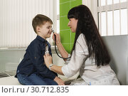 Купить «Врач-педиатр в шутку приложила стетоскоп к носу ребенка», фото № 30712835, снято 17 марта 2019 г. (c) Наталья Гармашева / Фотобанк Лори
