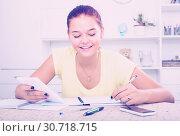 Купить «girl with smartphone doing homework», фото № 30718715, снято 6 декабря 2019 г. (c) Яков Филимонов / Фотобанк Лори