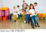 Купить «Positive female teacher playing circle game with children in classrom», фото № 30718971, снято 15 ноября 2018 г. (c) Яков Филимонов / Фотобанк Лори