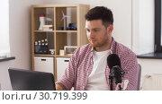 Купить «young man with laptop and microphone at home», видеоролик № 30719399, снято 2 мая 2019 г. (c) Syda Productions / Фотобанк Лори