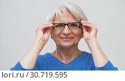 Купить «portrait of senior woman putting her glasses on», видеоролик № 30719595, снято 5 мая 2019 г. (c) Syda Productions / Фотобанк Лори