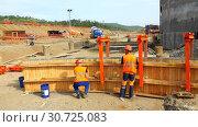 Купить «Workers in orange uniform and helmets erect timber formwork», видеоролик № 30725083, снято 2 июля 2016 г. (c) Aleksandr Sulimov / Фотобанк Лори