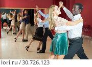Купить «Positive adult couples dancing tango together in modern studio», фото № 30726123, снято 4 октября 2018 г. (c) Яков Филимонов / Фотобанк Лори