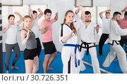 Купить «Young adult trainees practicing in karate class», фото № 30726351, снято 8 апреля 2017 г. (c) Яков Филимонов / Фотобанк Лори