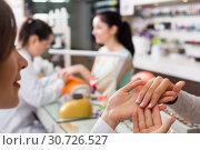 Купить «Manicurist inspecting female hands», фото № 30726527, снято 28 апреля 2017 г. (c) Яков Филимонов / Фотобанк Лори