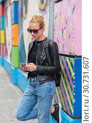 Купить «Woman using smartphone against colorful graffiti wall in New York city, USA.», фото № 30731607, снято 4 апреля 2020 г. (c) Matej Kastelic / Фотобанк Лори