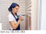 Штукатур штукатурит стену, нанося на нее имитацию кирпичной кладки. Стоковое фото, фотограф Иванов Алексей / Фотобанк Лори