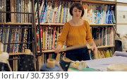 Купить «Competent saleswoman measuring ordered cloth for cutting in textile shop, preparing for sale», видеоролик № 30735919, снято 22 февраля 2019 г. (c) Яков Филимонов / Фотобанк Лори
