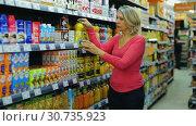 Portrait of mature woman choosing refreshing drinks on shelves in grocery shop (2019 год). Редакционное видео, видеограф Яков Филимонов / Фотобанк Лори
