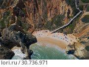 Купить «Aerial view of a sandy beach line full of bathers and colorful umbrellas on Do Camilo beach in Lacos, Algarve, Portugal», фото № 30736971, снято 29 апреля 2019 г. (c) Кирилл Трифонов / Фотобанк Лори
