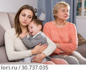 Купить «Two adult female are having disagreements with upbringing kid», фото № 30737035, снято 15 февраля 2018 г. (c) Яков Филимонов / Фотобанк Лори